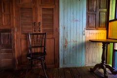 Alter Stuhl mit hölzerner Wand mit hellblauer Tür stockbild