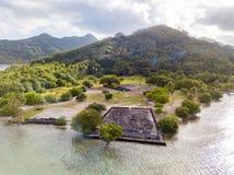 Alter Tempelkomplex Marae Taputapuatea auf dem Lagunenufer mit Bergen auf Hintergrund Raiatea-Insel Französisch-Polynesien, stockfotografie