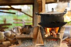 Alter Topf, der auf hölzernem brennendem Ofen steht Stockfotografie