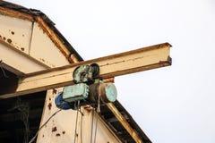 Alter Trägerkran mit großem Eisenhaken hebt schwere Last auf Riemen an lizenzfreie stockfotografie
