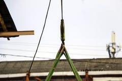 Alter Trägerkran mit großem Eisenhaken hebt schwere Last auf Riemen an lizenzfreie stockfotos