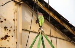 Alter Trägerkran mit großem Eisenhaken hebt schwere Last auf Riemen an stockfotografie