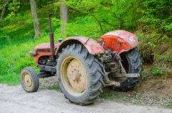Alter Traktor auf Landstraße lizenzfreie stockfotografie