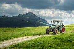 Alter Traktor auf Wiese Schöner Bergblick in den Alpen Stockfoto