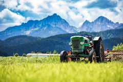 Alter Traktor in den Alpenwiesen Stockbild
