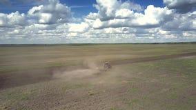 Alter Traktor eggt den grauen Feldboden, der durch Staubwolke umgeben wird stock footage