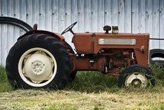 Alter Traktor, geparkt durch den Stall Stockfoto