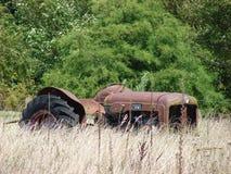 Alter Traktor im sehr langen trockenen Gras Stockbild