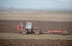Alter Traktor während des Pflügens Stockfotografie