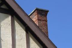 Alter Tudor Style Wall und Roofline mit Ziegelstein-Kamin lizenzfreies stockfoto