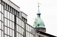 Alter Turm einer Kirche hinter dem hässlichen Glas-façade eines Neubaus Lizenzfreie Stockfotografie