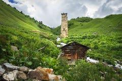 Alter Turm und Holzhaus Svan auf Strom des grünen Hügels und des Berges in Adishi bringen Dorf, Svaneti-Region in Georgia an Stockbild