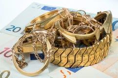 Alter und defekter Schmuck, Uhren des Goldes und Gold überzogen auf einem Hintergrund von Eurobanknoten lizenzfreie stockfotos