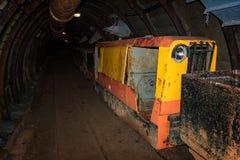 Alter und rostiger Metallbergwerkzug mit Lastwagen im Bergwerktunnel mit hölzernem Zimmern lizenzfreie stockbilder