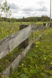 Alter verlassener Bretterzaun, ein Zaun, eine Wiese Stockfoto