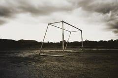 Alter verlassener Fußballzielbeitrag, der auf Feld steht Stockfotos