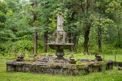 Alter verlassener ruinierter Brunnen in überwuchertem Park lizenzfreies stockbild