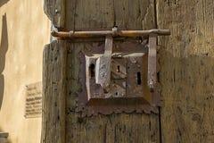 Alter Verschluss mit Klinke auf gealterter verschalter Tür. Lizenzfreie Stockfotografie