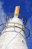 Alter verwitterter Leuchtturm gegen einen blauen Himmel Stockfoto
