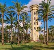 Alter verzierter antiker erhöhter Wasserbehälter gestaltet durch hohe Palmen vor Sonnenuntergang mit teils bewölktem blauem Himme stockbild