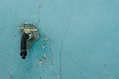 Alter Wasserhahn auf dem Hintergrund einer alten blauen Wand mit Sprüngen stockfoto