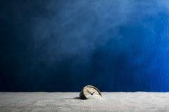 Alter Wecker auf Sand und blauem Hintergrund Lizenzfreie Stockfotografie