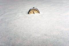 Alter Wecker auf Sand und blauem Hintergrund Stockbilder