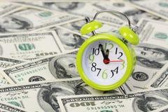 Alter Wecker, der auf Hintergrund des Geldes steht Stockfotografie