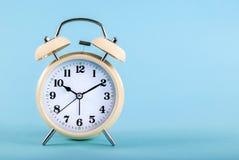 Alter Wecker lokalisiert auf einem blauen Hintergrund mit Raum für Text Stockbild
