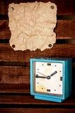 Alter Wecker und ein Blatt Papier auf der Wand stockfoto