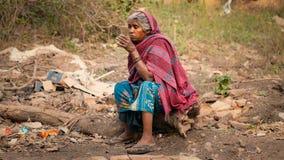 Alter weiblicher indischer Bettler, der Tee trinkt stockbild