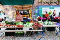 Alter weiblicher Marktverkäufer unter der Freiburg-Kathedrale, Deutschland Lizenzfreie Stockfotografie