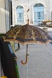 Alter Weinlese-Regenschirm auf der Straße Stockfotos