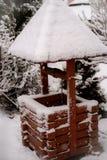 Alter Weinlesebrunnen mit einem Dach im Schnee im Winter stockfoto