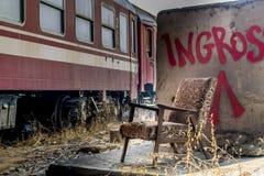 Alter Weinlesestuhl nahe rotem Zuglastwagen Stockfotos