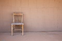 Alter westlicher Stuhl gegen eine Ziegelsteinwand Stockbilder