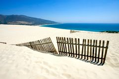 Alter Zaun, der aus verlassenen Dünen des sandigen Strandes heraus haftet Lizenzfreie Stockfotografie