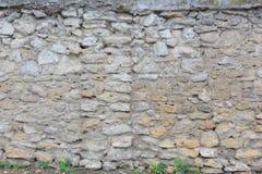Alter Zaun hergestellt von den grauen und beige Steinen als Hintergrund oder Hintergrund Lizenzfreie Stockfotos