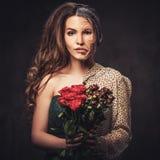 Altern, Hautpflegekonzept Halbe alte halbe junge Frau mit Blumenstrauß von roten Rosen Lizenzfreie Stockfotos