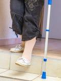 altern Sie Frau mit einer Krücke hinunter die Treppe stockfoto