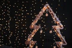 Alternatieve houten Kerstmisboom Een met de hand gemaakte Nieuwjaarboom met gloeilamp op slinger steekt zwarte achtergrond aan stock afbeeldingen
