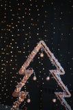 Alternatieve houten Kerstmisboom Een met de hand gemaakte Nieuwjaarboom met gloeilamp op slinger steekt zwarte achtergrond aan Le stock fotografie