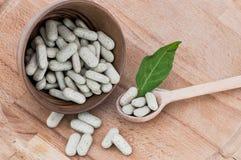 Alternatieve pillen op een houten lepel en in een kom, op houten lijst Stock Fotografie