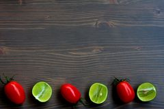 Alternating Tomatoes and Limes on Wood Background Stock Photos