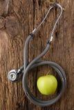 Alternativ medicin - stetoskop och gräsplanäpple på den wood bästa sikten för tabell optometriker för läkarundersökning för bakgr Arkivbild