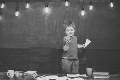 Alternative Bildung Lächelnder Junge, der geschmackvollen Apfel in seiner Hand betrachtet Blondes Kind, das Papierfläche hält Glü Lizenzfreies Stockfoto