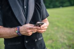 Alternative caucasion male in all black and rainbow bracelets while texting royalty free stock photography