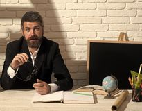 Alternative education and knowledge concept. Teacher and school supplies in classroom. Professor starts talking. And holds glasses. Man with beard on white stock photos