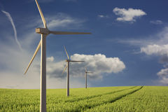 Alternative energies. Alternative energy - wind turbine in a wheat field Royalty Free Stock Image