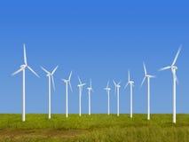 Alternative energy. Wind turbines on grass over blue sky Stock Photos